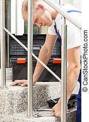 Man installing a bannister - Young working man tightening...