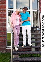 Care assistant helping a senior lady on steps holding her...