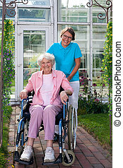 Smiling happy elderly lady in a wheelchair posing with an...