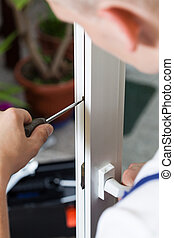 Handyman repairing window with screwdriver - Repairman...
