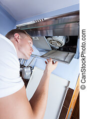 Handyman repairing kitchen extractor fan - Young repairman...