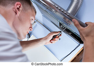 Repairman mending a kitchen extractor - Young handyman...
