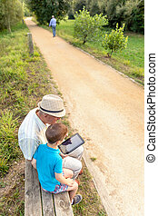 Grandchild and grandfather using a tablet outdoors -...