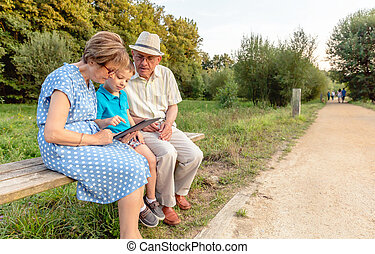 Grandchild and grandparents using a tablet outdoors -...