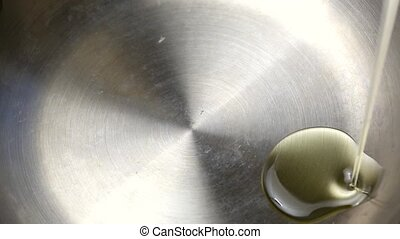 Olive oil pouring into frying pan - A very close view of...
