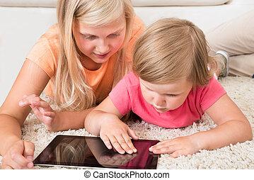 Kids Using Tablet Lying On Carpet