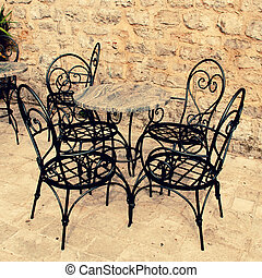 Mediterranean outdoor cafe - Iron table and chairs on...