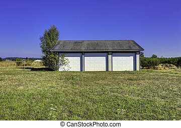 Three car garage with tile roof. Countryside landscape