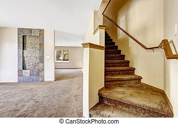 Staircase with carpet steps and wooden railing in empty...
