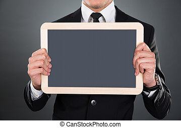 Midsection Of Businessman Holding Blank Slate - Midsection...