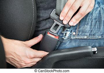 Man Fastening Seat Belt In Car - Closeup of man fastening...