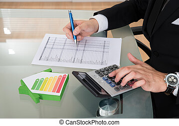 Businessman Calculating Energy Efficiency Rate - Cropped...