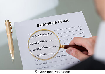 Businessman Examining Business Plan With Magnifying Glass -...