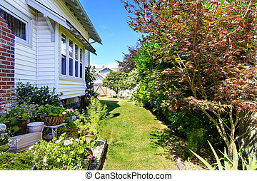 Backyard with flower bed and trees - Backyard area with...