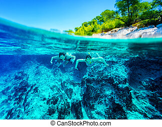 Active diver couple - Happy active couple diving near...