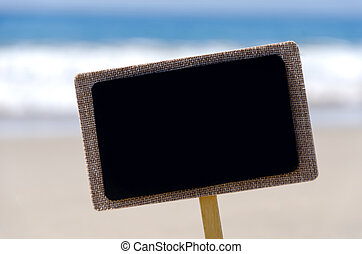 Nameplate on the sandy beach next to ocean