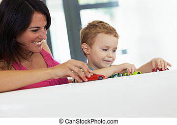 mom and child playing - mother and son playing with toy cars...