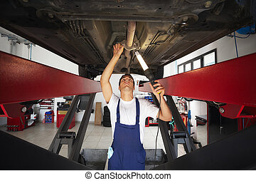 mechanic standing under car engine and holding lamp. Copy...