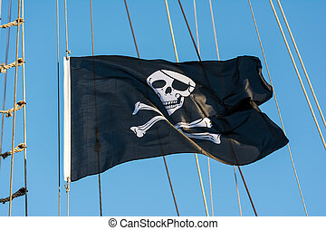 Black Pirate Flag With Human Skull On Blue Sky
