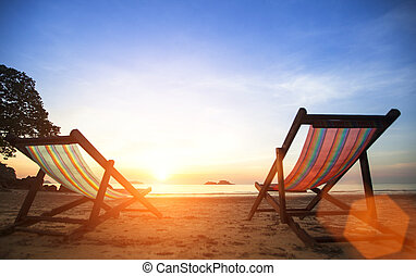 Pair beach loungers on the deserted coast sea at sunrise. Vacation concept.
