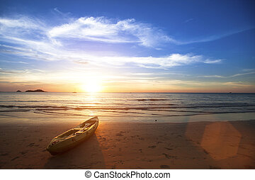 Amazing sunset on the ocean beach, canoe lying on the shore.