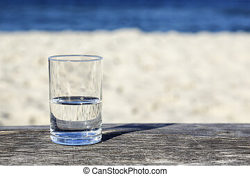 Glass of water which is half-full stands on a wooden table...