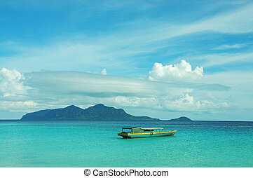 Boat on a sea coast with an island by the background