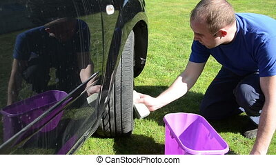 man clean car wheel - young man carefully clean wash his...