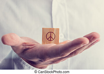 Man holding a wooden block with the peace sign balanced on...