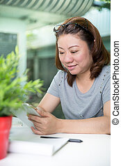 beautiful asian woman using tablet computer