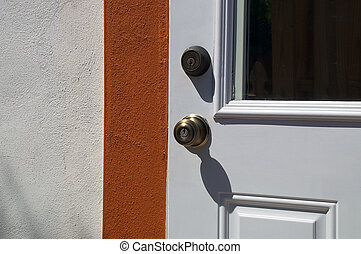 exterior door with knob and deadbolt in sunshine - Detail of...