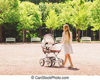 happy mother with stroller in park - family, child and...