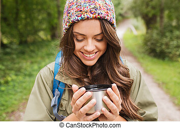 smiling young woman with cup and backpack hiking -...