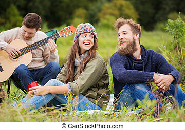 group of smiling friends with guitar outdoors - adventure,...