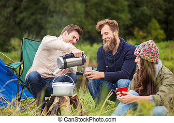 group of smiling friends cooking food outdoors - adventure,...