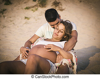 Happy Pregnant couple on beach outdoors. Couple is in the...