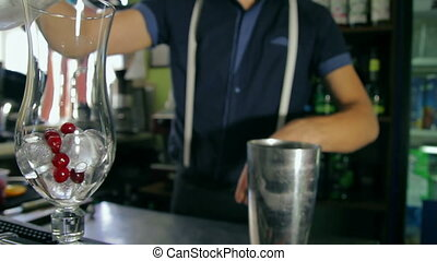 Bartender pouring glass with ice