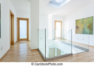 Stairs, glass banister and doors in modern hallway on the...