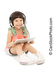 smiling little student girl sitting and holding a tablet