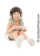 little student girl sitting and holding a tablet with earphone.