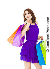 smiling young woman holding shopping bag over white...