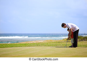 Family golf - Father teaching his son to play golf