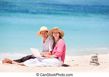 Wireless beach access - Happy couple using laptop on the...