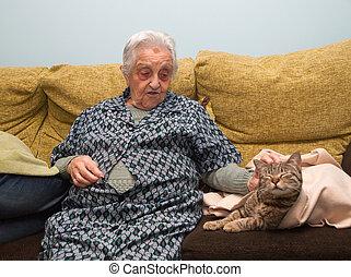 Elderly woman stroking her cat inside home.