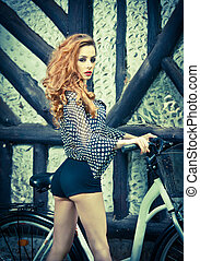 Sexy redhead with bike - Beautiful girl wearing ultramarine...