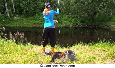 girl fishing pond cat - young woman fishing in the pond at...