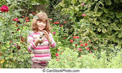 little girl cuddle kitten in the garden