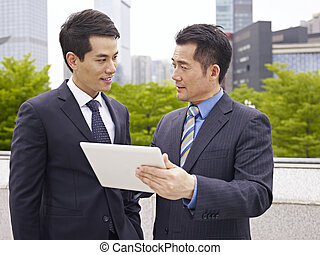 asian businesspeople - asian businessmen discussing business...