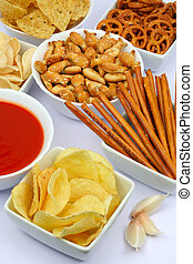Potato chips and other salty snacks on white background