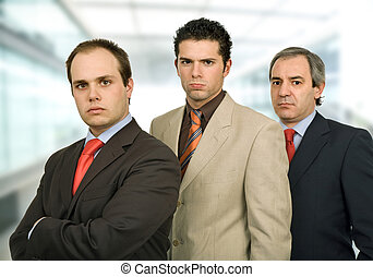 team - three business men standing at the office